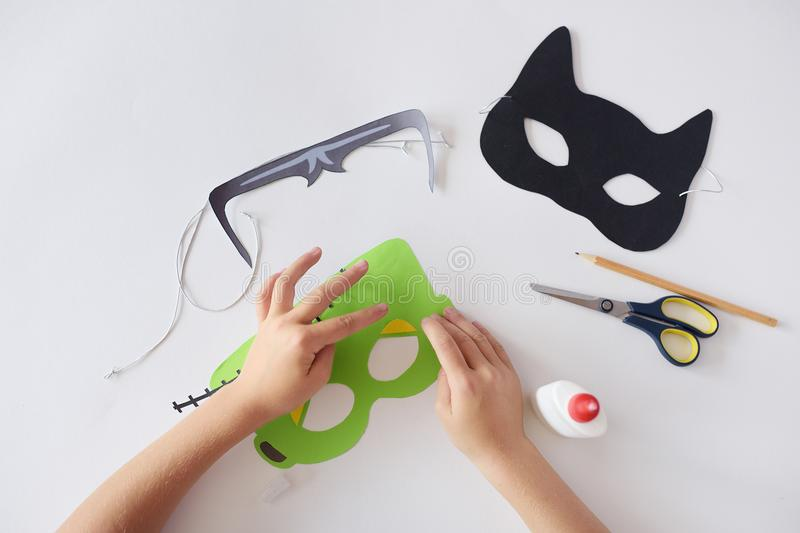 Making masks paper holiday Halloween Monster`s mask Black cat Hands top view stock photography