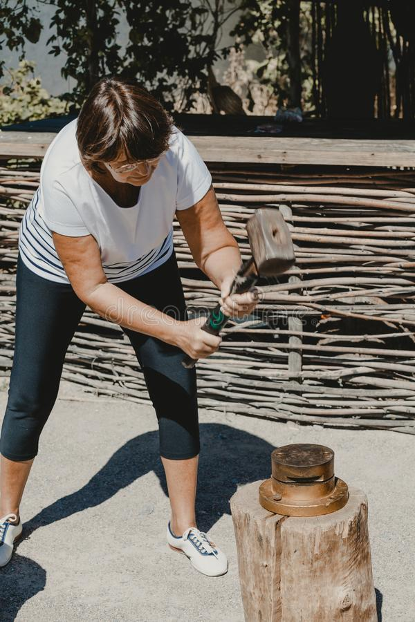 Woman beats large hammer on round die. Making a metal souvenir with your own hands. An adult woman strikes a large sledge hammer on a round punch on a stump royalty free stock photos