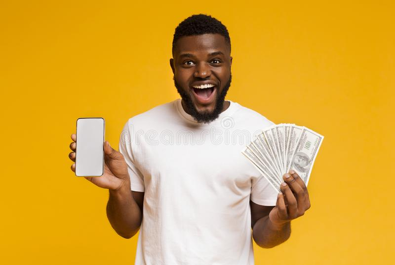 Happy guy working showing cellphone and bunch of money stock photos