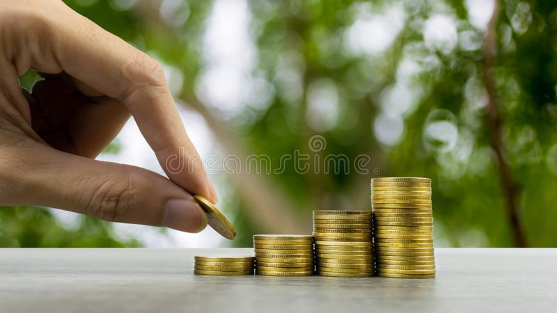 Making money and money investment concept. A man hand holding coin over stack of coins on wood table with nature background. Depicts long-term investment And stock image