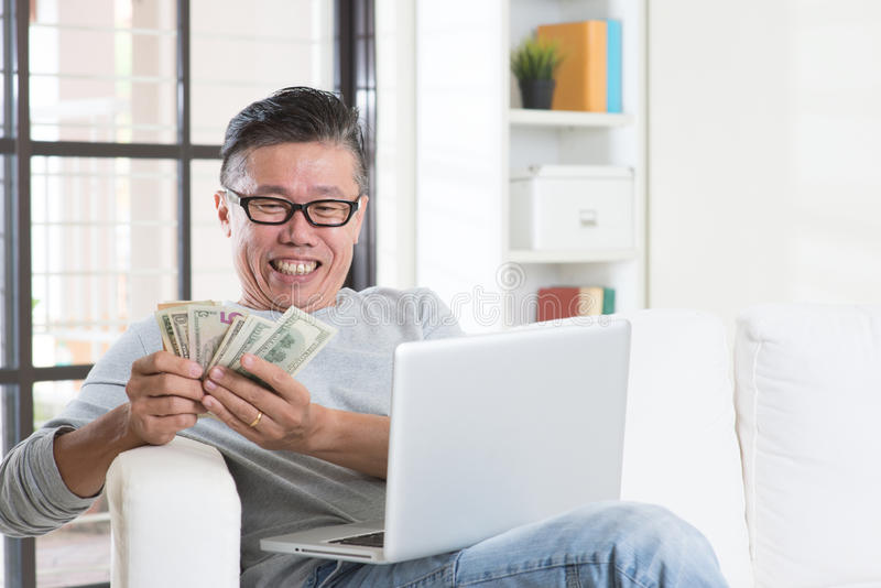 Making money from online business. Portrait of happy 50s mature Asian man using internet computer and counting cash at home, earning money from his successful royalty free stock image