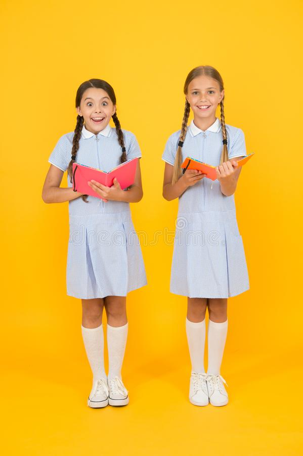 Making notes. small girls love literature. old school. happy friends in retro uniform. vintage kid fashion. back to. School. small girls hold workbook and stock image