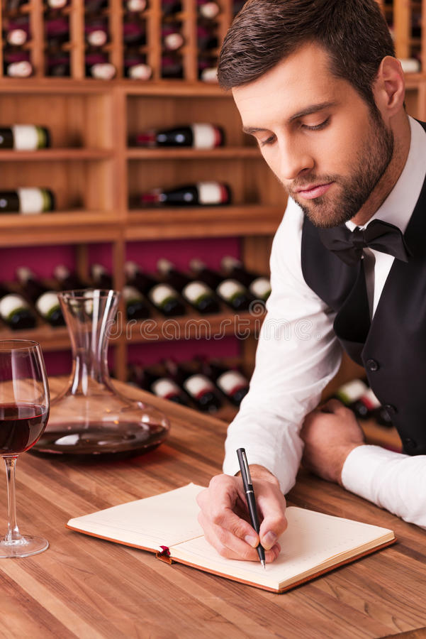 Making notes about wine. Confident male sommelier writing something in his note pad while leaning at the wooden table with wine shelf in the background royalty free stock image