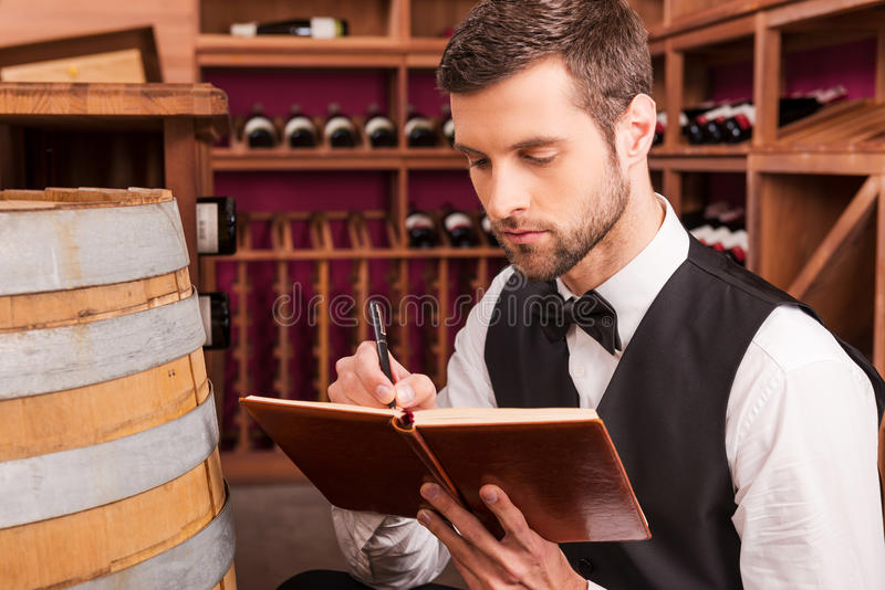 Making notes about wine. Confident male sommelier writing something in his note pad while sitting near the wine barrel royalty free stock photos