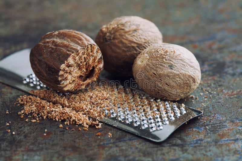 Making nutmeg powder. Macro view silver grater with grated muscat nuts. Kitchen still life photo. Shallow depth of field stock images