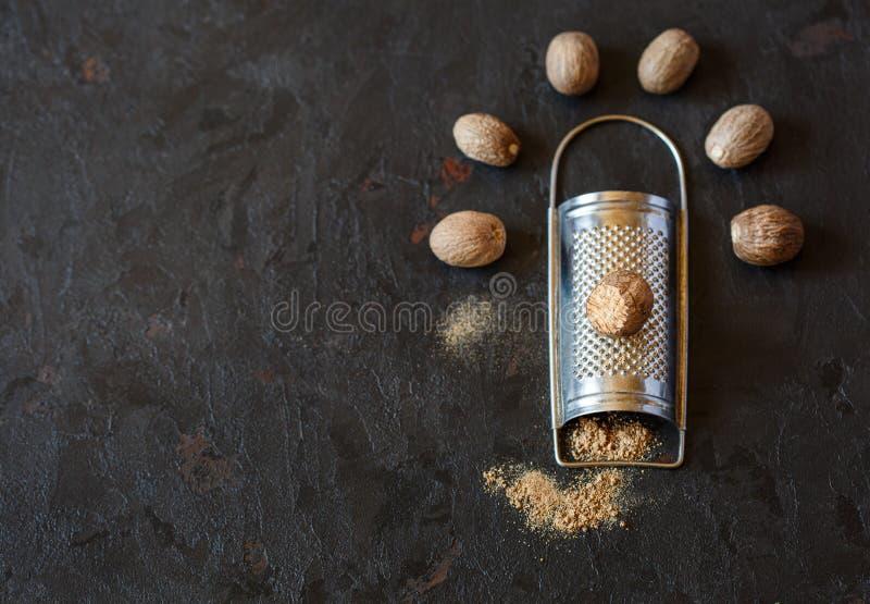 Making nutmeg powder process. Nutmeg on handly grater, heap ground powder nutmeg on old black background stock photo