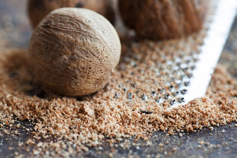 Making nutmeg powder process. Nuts silver grater. Kitchen still life photo. Shallow depth of field, aged brown rusty. Background. Selective focus royalty free stock photography
