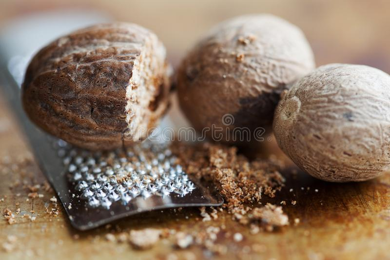 Making nutmeg powder process. Nuts silver grater. Kitchen still life photo. Shallow depth of field, aged brown rusty. Background. Selective focus stock photo