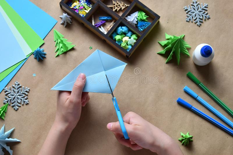 Making origami 3D Xmas tree with paper for decoration or greeting card. Merry Christmas and Happy New Year. Children DIY concept. Handmade crafts on holiday royalty free stock photos