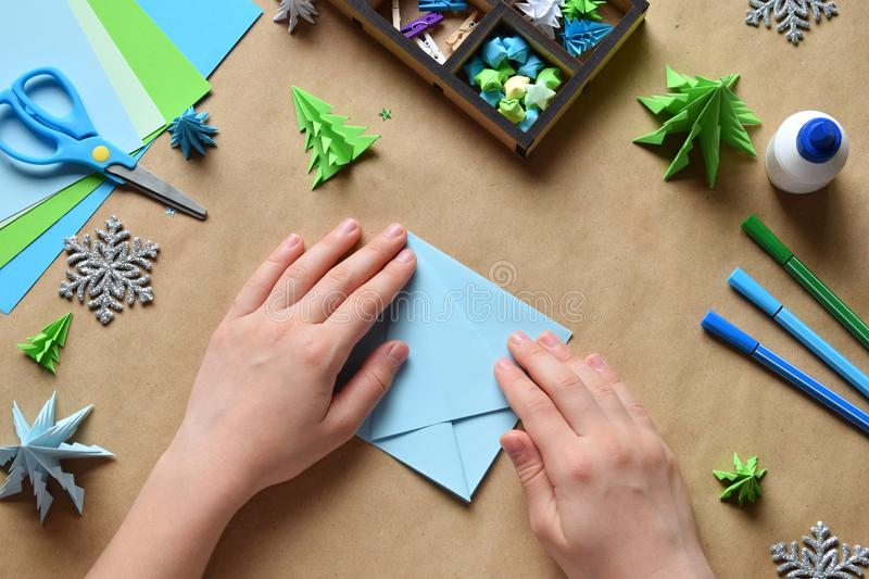 Making origami 3D Xmas tree with paper for decoration or greeting card. Merry Christmas and Happy New Year. Children DIY concept. Handmade crafts on holiday royalty free stock photography