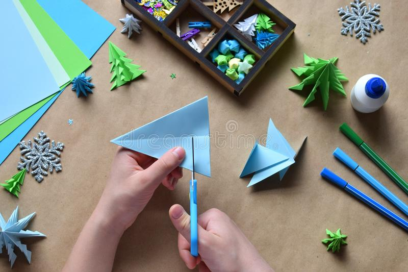 Making origami 3D Xmas tree with paper for decoration or greeting card. Merry Christmas and Happy New Year. Children DIY concept. Handmade crafts on holiday stock photos