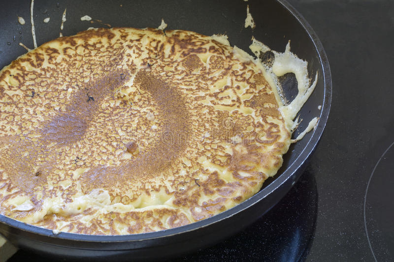 making pancakes in a black pan, fried until golden brown stock image