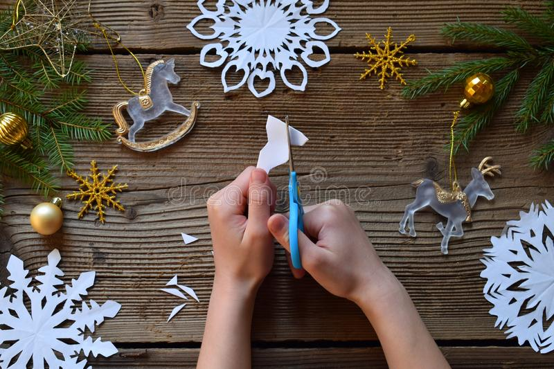Making paper snowflakes with your own hands. Children& x27;s DIY. Merry Christmas and New Year concept. Step 2. Cut the snowflake royalty free stock photos