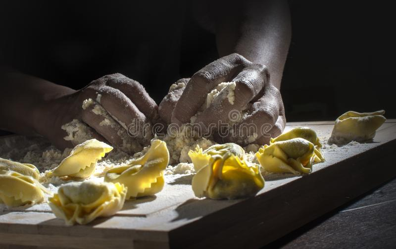 Making pasta by hand. Kneating pasta dough by hand, dropping ingredients royalty free stock images