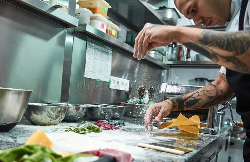 Making pasta process. Close up photo of concentrated chef with black tattoos on his arms pouring flour on kitchen table royalty free stock photo