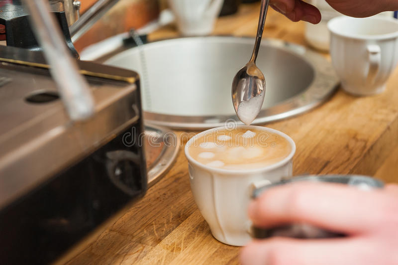 Making pattern in a cup of coffee. royalty free stock photos