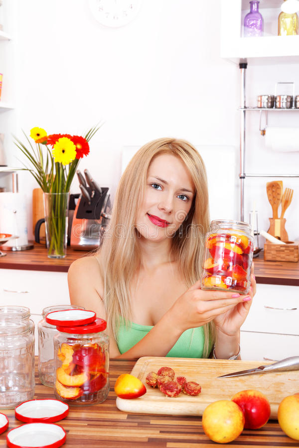 Making peach compote. Stunning blonde beauty in the kitchen making peach compote stock photography