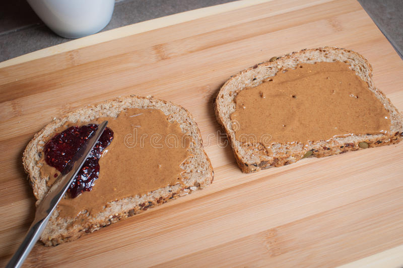 Making a Peanut Butter and Jelly Sandwich. How to make a peanut butter and jelly sandwich - spreading the jelly on the bread royalty free stock photos