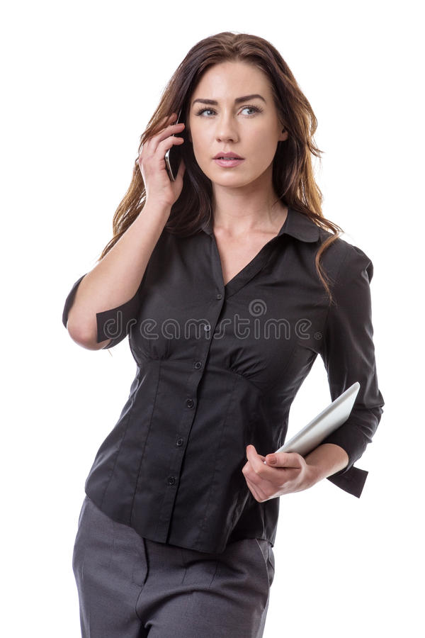 Making a phone call. Pretty young business woman holding a tablet computer and talking on her mobile phone at the same time stock photography