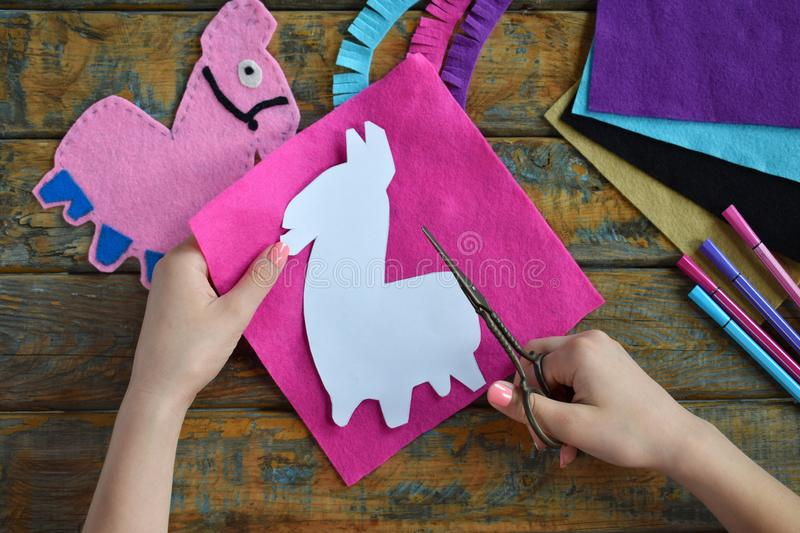 Making pink lama. Sewing toys from felt with your own hands. DIY concept for children. Handmade crafts. Step 1. Circle the stencil stock images