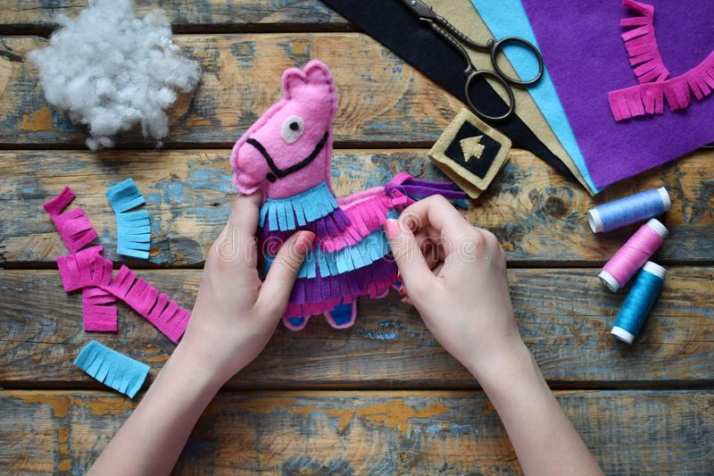 Making pink lama. Sewing toys from felt with your own hands. DIY concept for children. Handmade crafts. Step 5. Decorate the toy. Making the pink lama. Sewing royalty free stock image