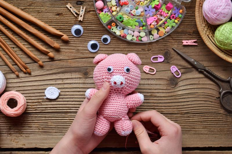 Making pink pig. Crochet toy for child. On table threads, needles, hook, cotton yarn. Step 2 - to sew all details of toy. Handmade. Crafts. DIY concept. Small stock image