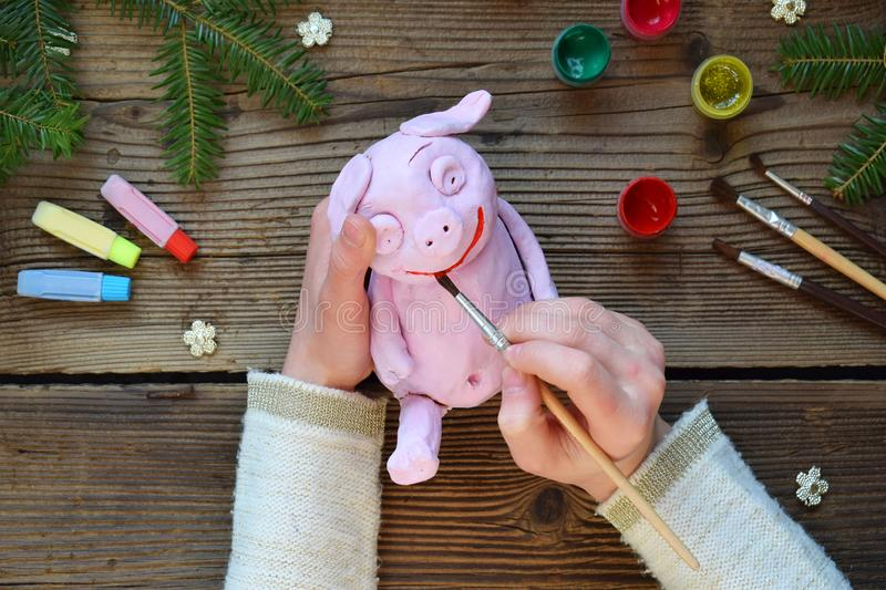 Making Pink pig, symbol of 2019. Painting clay toy with gouache. Creative leisure for children. Handmade crafts on holiday with stock photos