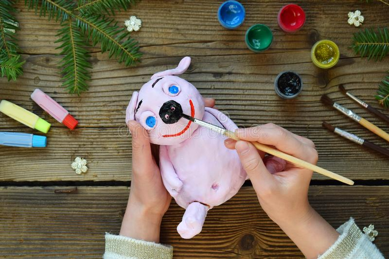 Making Pink pig, symbol of 2019. Painting clay toy with gouache. Creative leisure for children. Handmade crafts on holiday with stock photography