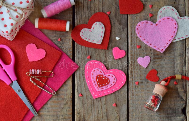 Making pink and red hearts of felt with your own hands. Valentine`s Day background. Valentine gift making, diy hobby. Children`s stock photo