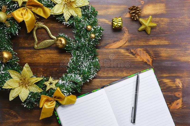 Making plans for Christmas and New Year flat lay. Notebook lying on wooden table royalty free stock images