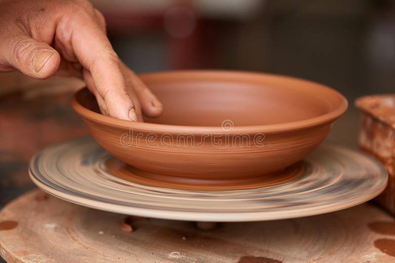 Making pottery on a potter`s wheel in the workshop, close-up, selective focus. Creative working process. Handmade masterpiece. Beautiful traditional clay art royalty free stock image