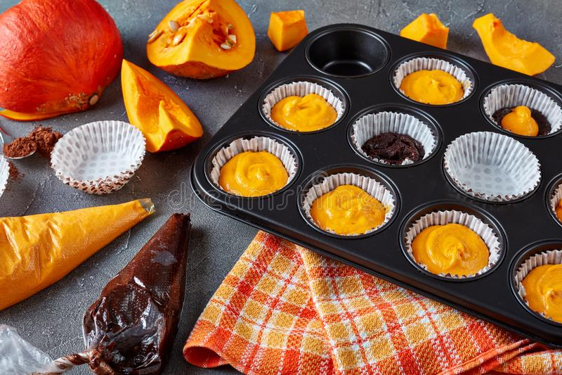 Making pumpkin chocolate muffins, close up royalty free stock images
