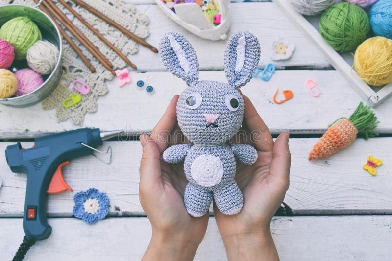 Making rabbit with carrot. Crochet bunny for child. On table threads, needles, hook, cotton yarn. Handmade crafts. DIY concept. Sm. All business. Income from royalty free stock image