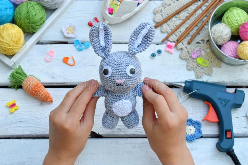 Making rabbit with carrot. Crochet bunny for child. On table threads, needles, hook, cotton yarn. Handmade crafts. DIY concept. Sm. All business. Income from stock images