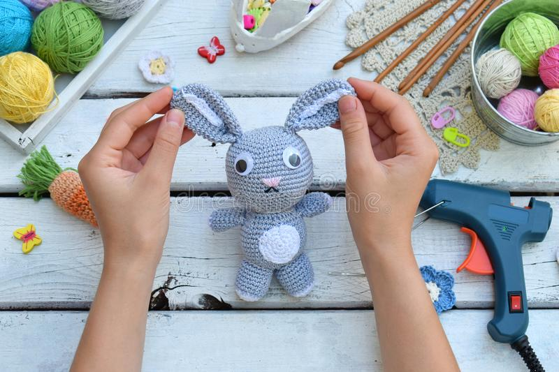 Making rabbit with carrot. Crochet bunny for child. On table threads, needles, hook, cotton yarn. Handmade crafts. DIY concept. Sm. All business. Income from stock photos