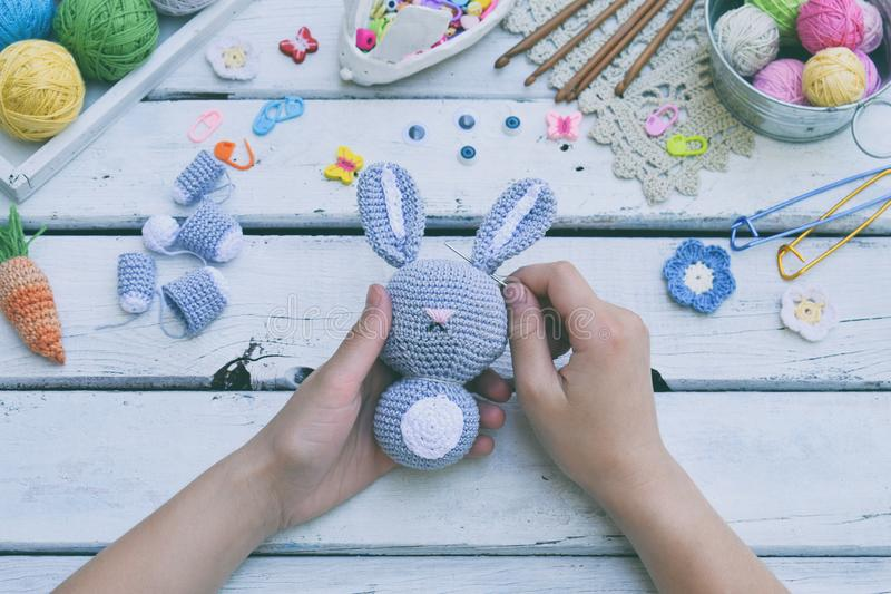 Making rabbit with carrot. Crochet bunny for child. On table threads, needles, hook, cotton yarn. Step 2 - to sew all details of t. Oy. Handmade crafts. DIY royalty free stock image