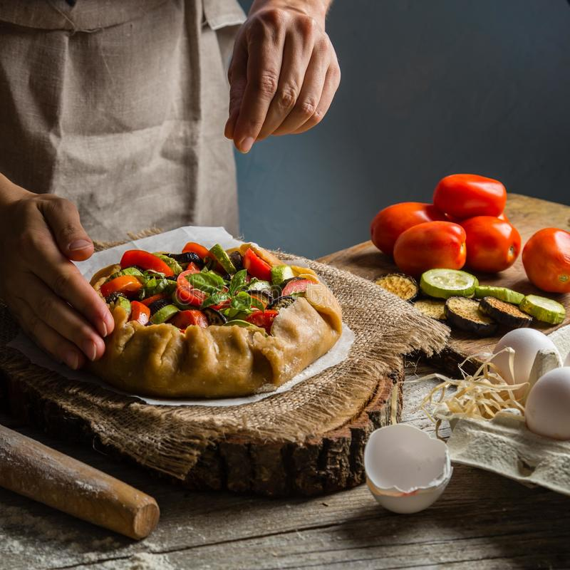 Making ratatouille galette pie. Hands on rustic background stock image