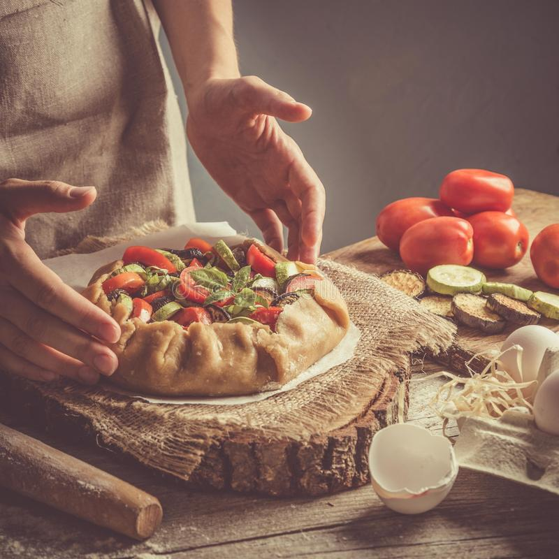 Making ratatouille galette pie. Hands, toned on rustic background royalty free stock images