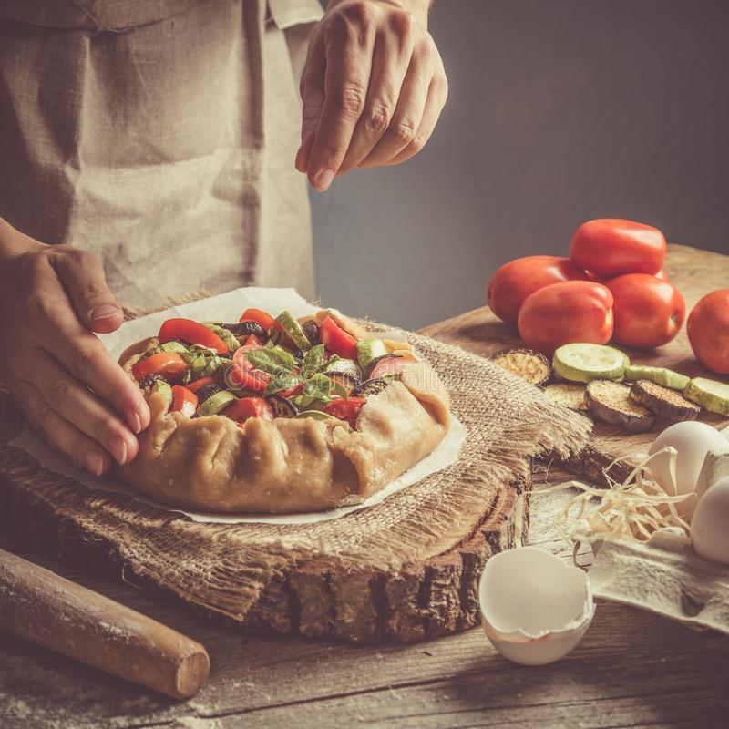 Making ratatouille galette pie. Hands, toned on rustic background royalty free stock photos