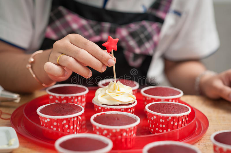 Making red velvet cupcakes. The action of making red velvet cupcakes. Woman hand stab down star shape fondant on cupcake stock photo