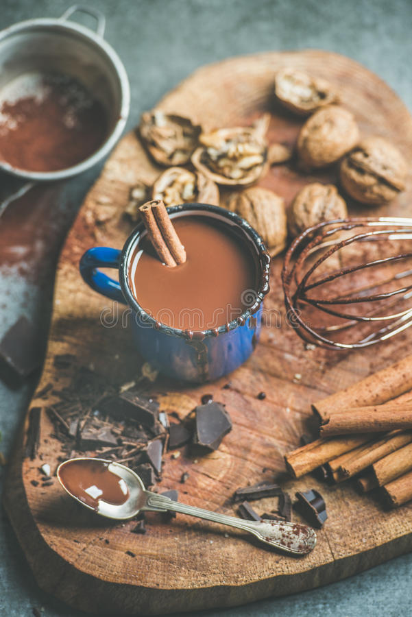 Making rich hot chocolate with cinnamon and walnuts royalty free stock photo