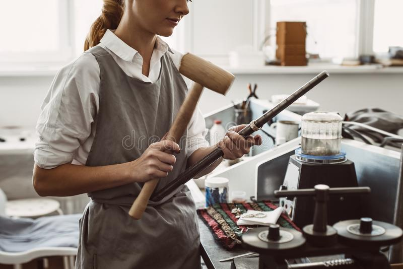 Making right size. Side view of female jewelry designer bending a silver blank on road using a mallet hammer stock photography