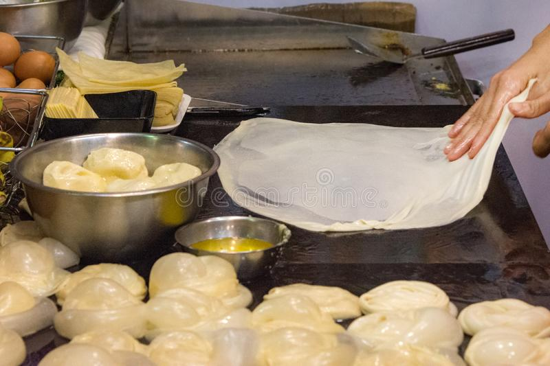 Making of Roti Canai, cooking process, Indian traditional street food royalty free stock photography