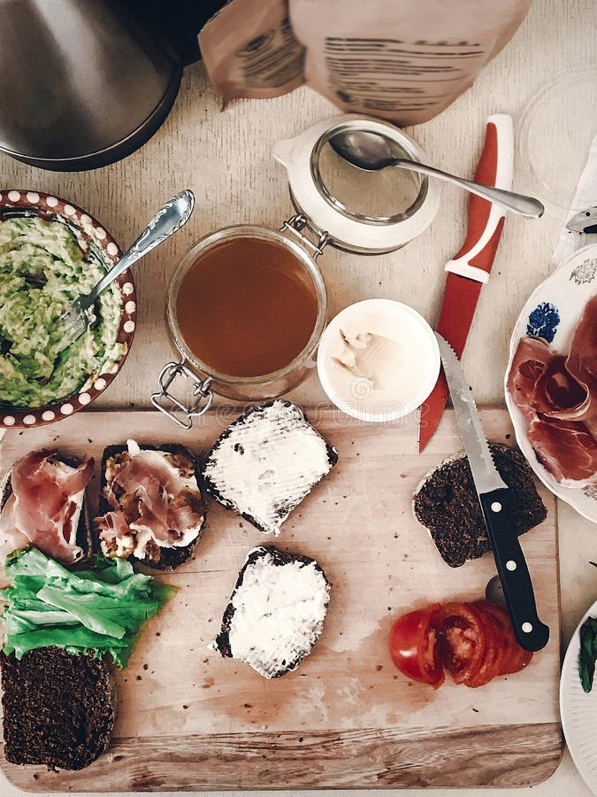 Making sandwich, italian canape with prosciutto tomatoes salad h. Oney basil and sauce, top view on wooden desk and knife. space for text. tasty appetizer stock photography