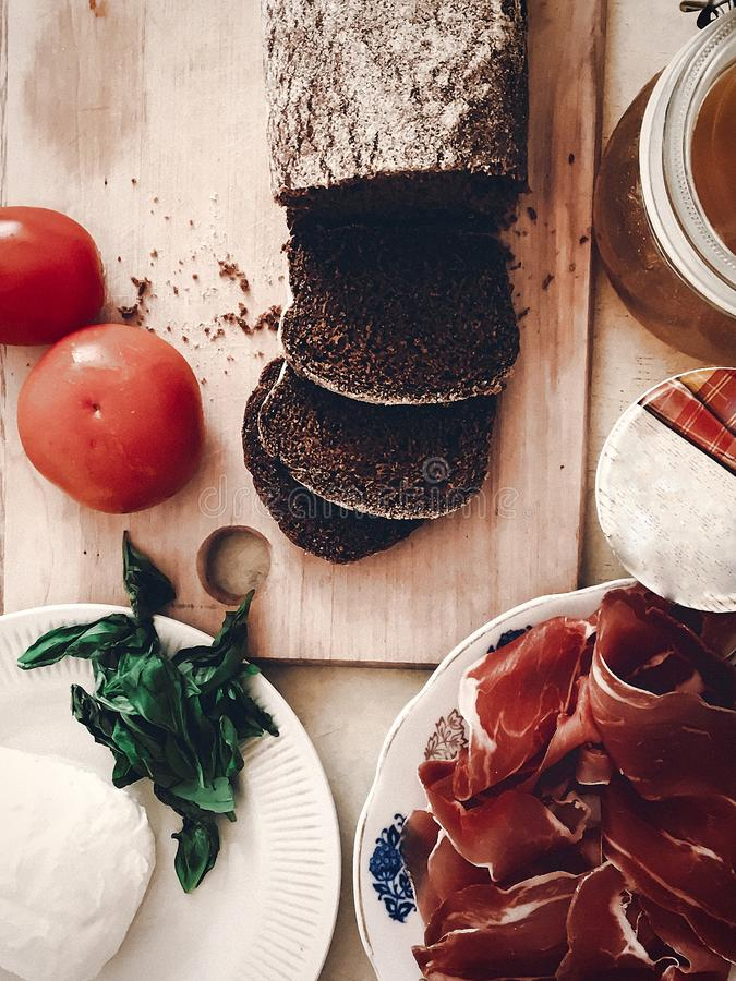 Making sandwich, italian canape with prosciutto tomatoes salad h. Oney basil and sauce, top view on wooden desk and knife. space for text. tasty appetizer stock image