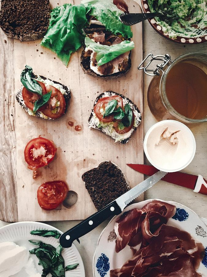 Making sandwich, italian canape with prosciutto tomatoes salad h. Oney basil and sauce, top view on wooden desk and knife. space for text. tasty appetizer royalty free stock photo