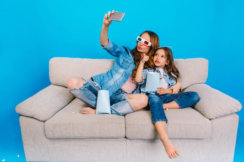 Making selfie portrait of pretty young mother with joyful daughter hugging and smiling to camera on couch on blue stock photos
