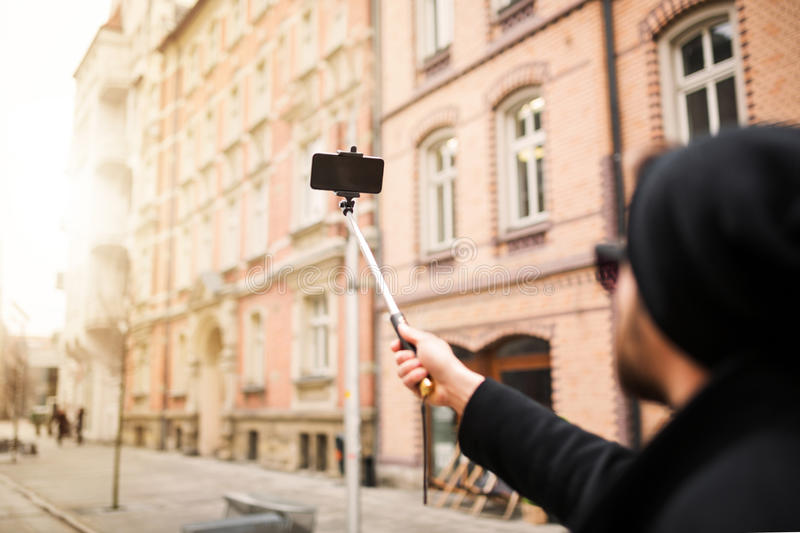 Making selfie in the town square. A photo of young, trendy man taking himself a photo by his mobile phone in the middle of the town square stock images