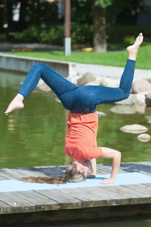 Making shirshasana outdoors. Young caucasian sporty woman making shirshasana outdoors royalty free stock images