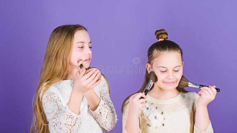 Making skin glow with makeup. Little makeup artists. Small girls applying makeup on face skin. Adorable children royalty free stock photo